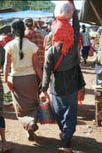 35K Jpeg 9809H33 Pa'O woman walking through Kalaw 5-day market, Shan State. This was the only Pa'O woman that I saw wearing leggings under her longyi. Also note the embroidered seam down the back of her blouse showing beneath her short jacket.