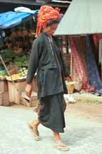 to 26K Jpeg 9809K01 Pa'O woman striding through the 5-day rotating market in Kalaw, Shan State. Her garments of black serge short, long-sleeved jacket with selvedge woven trim inset down the opening of the jacket, loose blouse with embroidered trim along the seams and calf length longyi are set off by the plaid scarf wound around her head and her striped bag