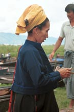 to 30K Jpeg 9809O12 Pa'O woman at Nampan 5-day rotating market, Lake Inle, Shan State. She is paying for her liquid fuel. Note the short serge jacket with details of the fabric woven in the selvedge used to trim the back seam and the edge of the front pocket. She is wearing the jacket over her loose blouse with embroidered seam trimmings. This is then worn over a longyis.