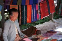 to Jpeg 55K Woman selling woven textiles in Kalaw 5 day rotating market, Shan State. There would appear to be some Silver Palaung woven striped tubeskirts hanging to the right of the photo.