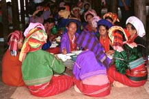 to 81K Jpeg Silver Palaung women eating the communal meal at the 'Full Moon day' festival in Pein Ne Bin village near Kalaw, southwestern Shan State. Note their traditional hand woven tube skirts, embroidered jackets, turbans and the bamboo rattan hoops around the waist, particularly of the woman on the right of the photo.