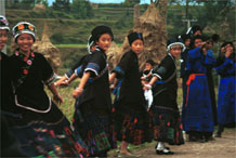 to Jpeg 50K  0110D17  Girls dancing and trumpeters playing as part of our welcome to Gan He village, Ya Rong township, Huishui county, Guizhou province, south-west China. The people living in this village are known as Qing Miao. There has been much intermarriage between Miao and Bouyei which is evident from the every-day costume of the women. The pieced skirts of applique and wax-resist being worn by the girls were originally only worn at funerals but today they are worn for special festivals and dance competitions.