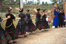 to Jpeg 57K  0110D18A Girls dancing as part of our welcome to Gan He village, Ya Rong township, Huishui county, Guizhou province, south-west China. The people living in this village are known as Qing Miao. There has been much intermarriage between Miao and Bouyei which is evident from the every-day costume of the women. The pieced skirts of applique and wax-resist being worn by the girls were originally only worn at funerals but today they are worn for special festivals and dance competitions.