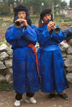 to Jpeg 56K  0110D31 Two trumpeters as part of our welcome to Gan He village, Ya Rong township, Huishui county, Guizhou province, south-west China. The people living in this village are known as Qing Miao. There has been much intermarriage between Miao and Bouyei which is evident from the costume of the women.