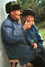 to Jpeg 56K  0110D32 Two old men watching our welcome to Gan He village, Ya Rong township, Huishui county, Guizhou province, south-west China. The people living in this village are known as Qing Miao.
