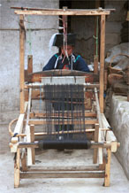 to Jpeg 56K 0110E02  Woman weaving an indigo plaid fabric on an upright heddle loom in Gan He village, Ya Rong township, Huishui county, Guizhou province, south-west China. The people living in this village are known as Qing Miao. There has been considerable intermarriage between Miao and Bouyei and the costume is very mixed.