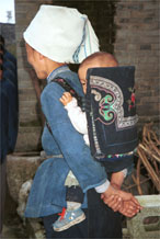 to Jpeg 56K  0110E16 A baby held in an attractive baby carrier with embroidery and applied braid in Gan He village, Ya Rong township, Huishui county, Guizhou province. This is a Qing Miao (or Bouyei/Miao as there has been much intermarriage and the costume is very mixed).