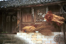 to Jpeg 57K 0110E18  The harvest drying outside a house in Gan He village, Ya Rong township, Huishui county, Guizhou province. This is a Qing Miao (or Bouyei/Miao as there has been much intermarriage and the costume is very mixed).