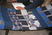 to Jpeg 57K  0110E22 A length of pieced fabric ready to be made up into a skirt. Note the wax resist in two shades of indigo, embroidered work and applied plaid triangles of cloth, Gan He village, Ya Rong township, Huishui county, Guizhou province. This is a Qing Miao (or Bouyei/Miao as there has been much intermarriage and the costume is very mixed).