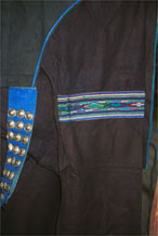 toJpeg 55K  0110E23  Part of a woman's indigo jacket showing an inserted band of weaving in the sleeve and silver buttons on the fastening in Gan He village, Ya Rong township, Huishui county, Guizhou province. This is a Qing Miao (or Bouyei/Miao as there has been much intermarriage and the costume is very mixed).