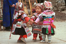 to Jpeg 125K Iron beating Miao festival costume in miniature worn by little girls dancing in Gao Zhai village, Bai Jin township, Huishui county, Guizhou province. Note the finely gathered hat crown worn by the little girl on the right and shown in closeup in photos further down in the photo gallery 0110C08