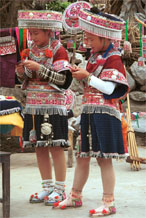 to Jpeg 176 Two Iron beating Miao women in Gao Zhai village, Bai Jin township, Huishui county, Guizhou province working on some embroidery and showing off their festival costume against a back drop of an even brighter hat and two of their jackets 0110C09