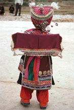 to Jpeg 129K Iron beating Miao festival costume in miniature worn by one of little girls who danced for us in Gao Zhai village, Bai Jin township, Huishui county, Guizhou province. She is wearing what looks like a very ornate baby carrier on her back 0110C15
