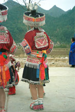 to Jpeg 158K Back view of Iron beating Miao women's costume in Gao Zhai village, Bai Jin township, Huishui county, Guizhou province against the backdrop of the farm land and mountains rising from the narrow valley 0110C17