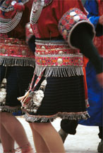 to Jpeg 143K Close-up of Iron beating Miao women's costume in Gao Zhai village, Bai Jin township, Huishui county, Guizhou province showing the finely woven, striped skirt and the brightly embroidered braids around the waist 0110C20