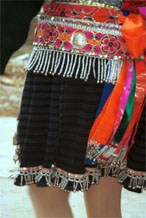to Jpeg 133K Close-up of Iron beating Miao women's costume in Gao Zhai village, Bai Jin township, Huishui county, Guizhou province showing the finely woven, striped skirt and the brightly embroidered braids around the waist 0110C21