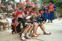 to Jpeg 138K Iron beating Miao women in Gao Zhai village, Bai Jin township, Huishui county, Guizhou province working on some embroidery and wearing their festival finery watched by the musicians 0110C28