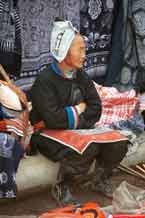 to Jpeg 57K 0111G30 Gejia woman sitting amongs her modern wax resist work made to sell to the tourists. Note her embroidered apron which is edged with some original wax resist. Her headdress is, however, made from a commercially manufactred fabric using traditional Gejia designs. Ma Tang village, Kaili City, Guizhou