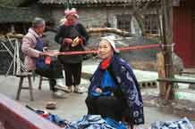 to Jpeg 58K 0111G35 Gejia women weaving braids, knitting hairnets and sewing by a heap of wax resist clothing.  Ma Tang village, Kaili City, Guizhou province.