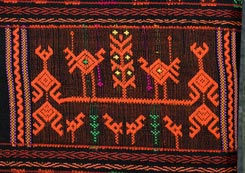 "Jpg 161K - A design on a cloth is for the tourist market, rather gaudy and with large, widely spaced designs (for ease and speed of production I expect), but Chris thinks that the basic technique is the same used to make most Li minority supplementary weft weavings. Note in areas which are left without design the weft underneath tends to show through (see green threads in this design), which is somewhat inelegant, and may explain why good, old Li weavings tend to have very dense designs without much ""ground"" visible."