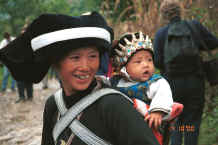 Jpeg 31K Side comb Miao woman and baby showing the baby's hat sporting protective white metal Buddhas - Long Dong village, De Wo township, Longlin country, Guangxi province 0010d32.jpg