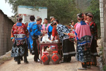 to Jpeg 94K Miao women getting ready to greet with alchohol and lusheng pipes as we enter Lou Jia Zhuang village, Anshun city, Guizhou province. Note the flowers in the wax resist on their festival clothing which may be the reason that are sometimes called 'Flower Miao'. 0110A12