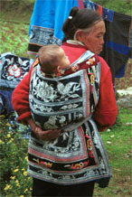 Jpeg 107K Miao woman with baby in waxed (batik) and embroidered baby carrier in Lou Jia Zhuang village, Anshun city, Guizhou province 0110B04