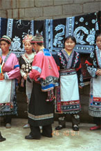 to Jpeg 116K Group of Miao women wearing a mixture of clothing including wax resist (batik) and embroidery. The traditional costume has absorbed styles from other Miao as well as other influences. Note the traditional festival hair styles of some of the women. Lou Jia Zhuang village, Anshun city, Guizhou province 0110B12a
