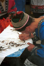 to Jpeg 73K Miao woman wearing festival costume and hair style using her la dio (literally 'wax knife') to apply the wax resist la ran (literally 'wax dye') in a floral style. Lou Jia Zhuang village, Anshun city, Guizhou province 0110B19