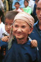 Jpeg 28K Old White Miao lady, probably with her grandson on her back and her son behind her in the crowd to welcome us to Ma Wo village, Zhe Lang township, Longlin county, Guangxi province 0010j03.jpg