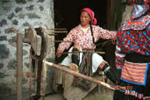 Jpeg 43K White Miao woman spinning 5 reels of hemp or ramie onto spindles after initial splicing - Ma Wo village, Zhe Lang township, Longlin county, Guangxi province. 0010j12.jpg