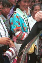 Jpeg 37K White Miao women standing with appliqued head pieces and showing fine applique (reverse applique) on jacket armbands - a style which is used on both head pieces, waist ties and jacket armbands - Ma Wo village, Zhe Lang township, Longlin county, Guangxi province 0010j27.jpg