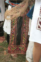Jpeg 35K Front view of a White Miao woman showing her machine embroidered apron over a pleated hemp or ramie woven skirt over which is draped hemp or ramie fibre stripped from the bush which she is splicing as she stands and waits - Ma Wo village, Zhe Lang township, Longlin county, Guangxi province 0010j37.jpg