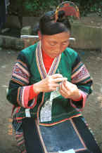 Jpeg 34K Side Comb Miao married woman finishing off a paper cut-out for embroidery probably for a sleeve insert - Pao Ma Cheng village, Teng Jiao township, Xingren country, Guizhou province 0010n27.jpg