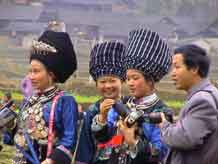 to Jpeg 46K Miao women dressed in their festival finery and examining cameras a village in Songtao Miao Autonomous County, Tongren Prefecture, eastern Guizhou Province.
