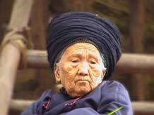 to Jpeg 37K An old woman, wearing her turban which may be between 6-10 metres in length, watching the festivities in a Miao village in Songtao Miao Autonomous County, Tongren Prefecture, eastern Guizhou Province.