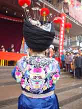 to Jpeg 48K Back view of a Miao girl at a festival in a village in Songtao Miao Autonomous County, Tongren Prefecture, eastern Guizhou Province. Note the silver decorations peeping out of the headdress and the bold embroidery collar covering the back of the blouse.