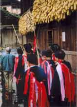 to Jpeg 57K e27e 25 February 2004, the fourth day of the festival, in Langde village, Guizhou province, On this day, the ceremony was to take the spirit of the mountain dragon inside each home to live there so the family would enjoy good fortune in the future. The shaman and a group of men all wore traditional dress. These men were the leading people of the ceremony and of the community. They must be well thought of by the villagers before they can be selected as participants or else they cannot play the roles. When the ceremony started, the shaman went in front leading the way to each home. On entering each family's house they were offered cups of rice wine by the head of the family and fire crackers were also set off. While in the house, they played lusheng and danced in a circle to the rhythm of the bronze drum. When leaving the house, the owner gave them some red ribbons and cigarettes.