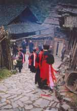 to Jpeg 57K e30e 25 February 2004, the fourth day of the festival, in Langde village, Guizhou province, On this day, the ceremony was to take the spirit of the mountain dragon inside each home to live there so the family would enjoy good fortune in the future. The shaman and a group of men all wore traditional dress. These men were the leading people of the ceremony and of the community. They must be well thought of by the villagers before they can be selected as participants or else they cannot play the roles. When the ceremony started, the shaman went in front leading the way to each home. On entering each family's house they were offered cups of rice wine by the head of the family and fire crackers were also set off. While in the house, they played lusheng and danced in a circle to the rhythm of the bronze drum. When leaving the house, the owner gave them some red ribbons and cigarettes.