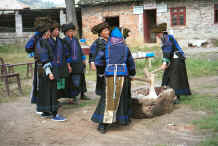 Jpeg 41K Black Miao women kneading stick rice served for festivals.  Note the young women with their heavy earings held by braid and the older women wearing them in pierced earlobes.  The gentian violet dyed back apron and the small insets of gentian dyed silk satin around the embroidered back panel of the jacket are clearly visible.  Zuo Qi village, Min Gu township, Zhenfeng county, Guizhou province 0010q04.jpg