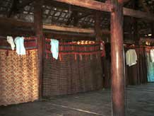 12. to Jpeg 34K Curtains separating off the sleeping areas from each other and from the living area in a Black Thai (Tai Dam) House.in Dien Bien Phu, Lai Chau Province, Vietnam. The curtains show various styles of decorative heading bands. The main fabric in the curtain second from the left is probably a hand-woven cotton plaid fabric. October 1995.