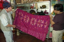 to Jpg 63K Nick Fielding examining an old silk malong at the Aljamelah Inaul Weaving and Sewing Center - Mindanao, 2007