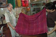 to Jpg 60K Nick Fielding examining an old silk textile at the Aljamelah Inaul Weaving and Sewing Center - Mindanao, 2007