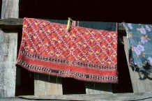 to Jpeg 31K A Sgaw Karen traditional woman's blouse hanging out to dry showing at the bottom the koh dyed (red) cotton embroidery and added Jacob's seeds on the indigo dyed, hand woven base 8812o35B.jpg