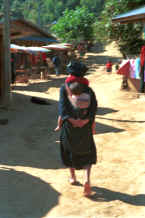 to Jpeg 26K A grandmother carrying her grandchild in a baby carrier on her back in a village in the hills around Chiang Rai 8812q28.jpg