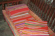 to Jpeg 47K A roll of weaving for cutting into bag lengths and cushion and mattress ends, Black Thai village, Dien Bien Phu, Lai Chau Provine.  Note the cushion edge using similar weaving just showing which has been covered by a protective raffia mat. 9510D02.JPG