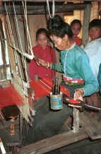 to Jpeg 35K Black Thai woman, watched by her children, demonstrating weaving on a length of weaving for bags and bedding/cushion ends in a village near Dien Bien Phu, Lai Chau Province 9510D19.JPG