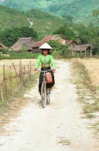 to Jpeg 41K Black Thai young woman cycling out of her village wearing a straw hat over her head dress to give added protection from the sun.  Dien Bien Phu, Lai Chau Province. 9510D36.JPG