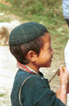 Jpeg 46K Young Black Hmong boy near a school in the hills of Sa Pa, Lao Cai Province - note the embroidered collar on his jacket.  In common with many Hmong groups in Vietnam and Thailand the embroidery is on the underside of the collar. 9510I37.JPG