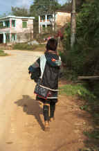to Jpeg 35K Black Hmong mother carrying her baby in a carrier walking out of Sa pa, Northern Vietnam, to her home village 9510I23